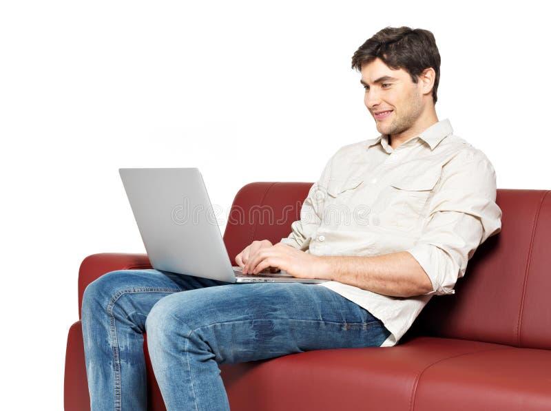 Το χαμογελώντας ευτυχές άτομο με το lap-top κάθεται στο ντιβάνι στοκ φωτογραφίες