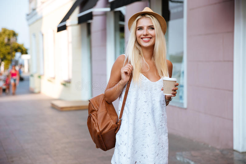 Το χαμογελώντας εύθυμο ξανθό κορίτσι στην εκμετάλλευση φορεμάτων παίρνει μαζί το φλυτζάνι στοκ εικόνες με δικαίωμα ελεύθερης χρήσης
