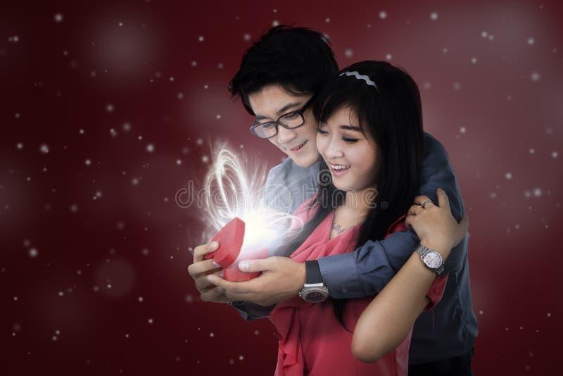 Το χαμογελώντας ζεύγος ανοίγει ένα δώρο στοκ φωτογραφία