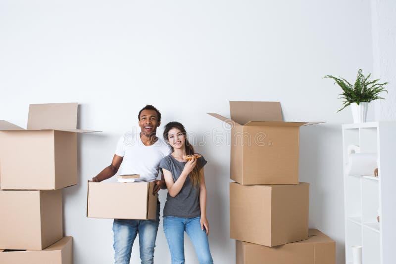Το χαμογελώντας ζεύγος ανοίγει τα κιβώτια στο νέο σπίτι στοκ φωτογραφία