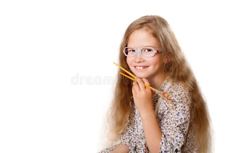 Το χαμογελώντας κορίτσι κρατά ιαπωνικά chopsticks στοκ εικόνα