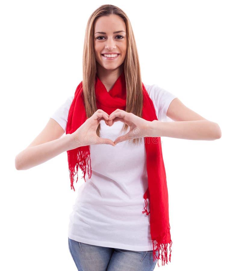 Το χαμογελώντας κορίτσι παρουσιάζει καρδιά με τα χέρια στοκ φωτογραφία