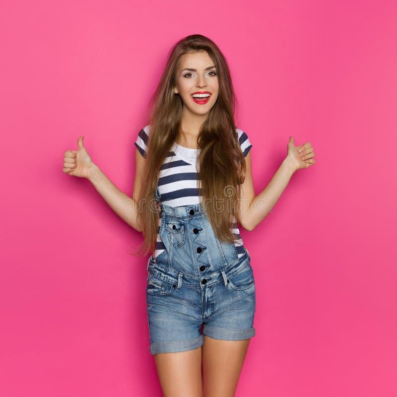 Το χαμογελώντας κορίτσι στην παρουσίαση Dungarees φυλλομετρεί επάνω στοκ φωτογραφία