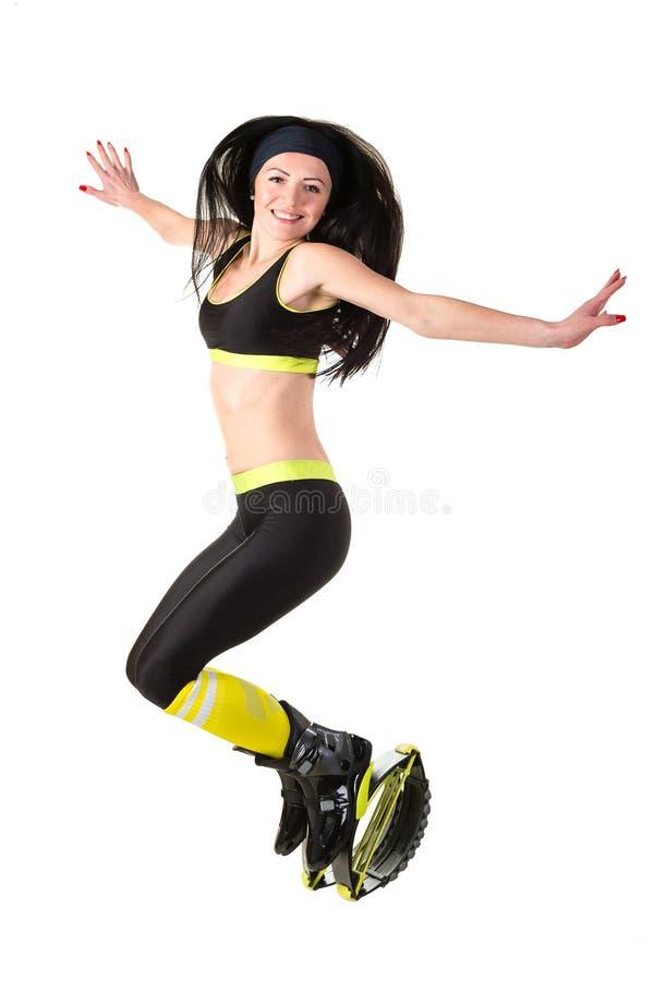 Το χαμογελώντας κορίτσι brunette με το μακρυμάλλες άλμα σε ένα kangoo πηδά στοκ εικόνες