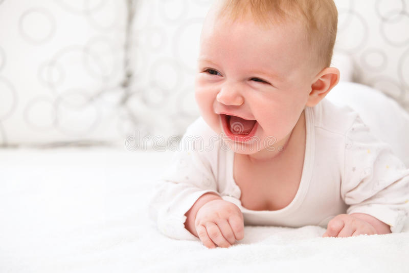 Το χαμογελώντας κοριτσάκι βρίσκεται στο κρεβάτι στοκ φωτογραφίες