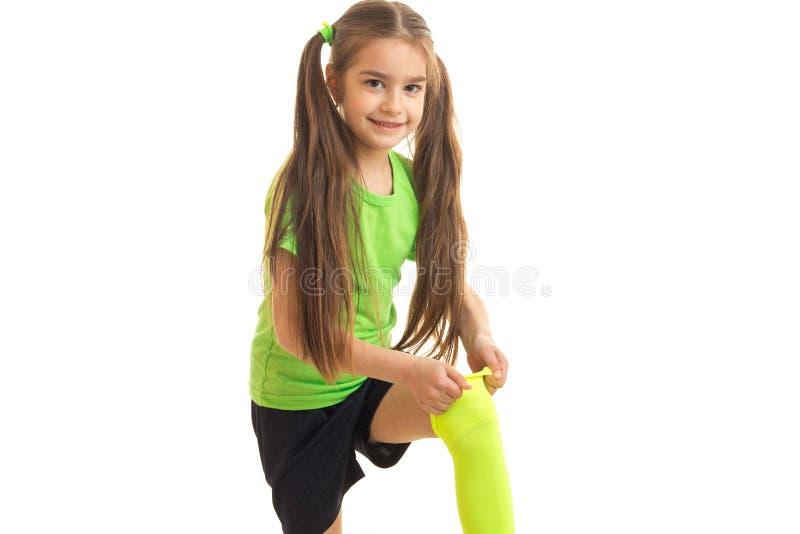 Το χαμογελώντας μικρό κορίτσι με τις ουρές βελτιώνει τις αθλητικές γόνατο-ψηλά στοκ εικόνα με δικαίωμα ελεύθερης χρήσης