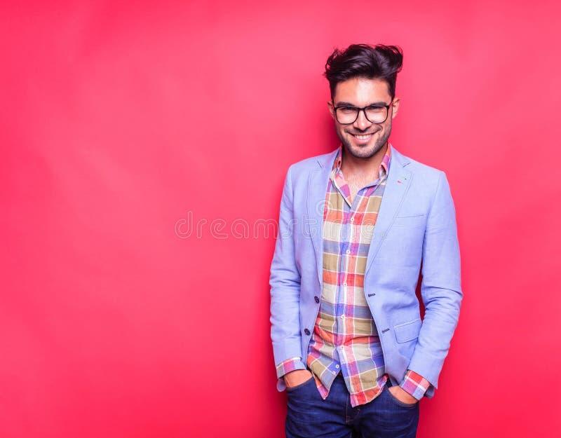 Το χαμογελώντας νέο άτομο μόδας που κρατά δικών του παραδίδει τις τσέπες στοκ φωτογραφία με δικαίωμα ελεύθερης χρήσης