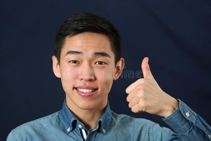 Το χαμογελώντας νέο ασιατικό άτομο που δίνει τους αντίχειρες υπογράφει επάνω στοκ φωτογραφία