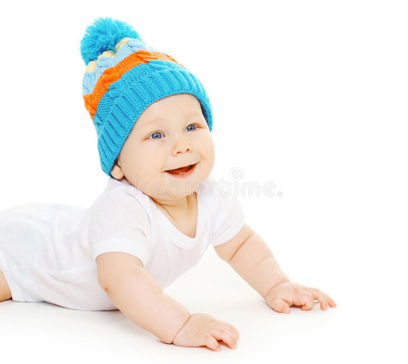 Το χαμογελώντας χαριτωμένο μωρό σέρνεται στο πλεκτό καπέλο στοκ εικόνες