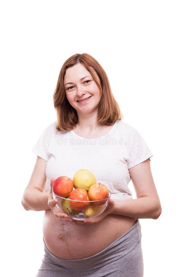 Το χαμόγελο εγκύων γυναικών στη κάμερα κρατά ένα κύπελλο γυαλιού με τα φρούτα στα χέρια της στοκ εικόνες