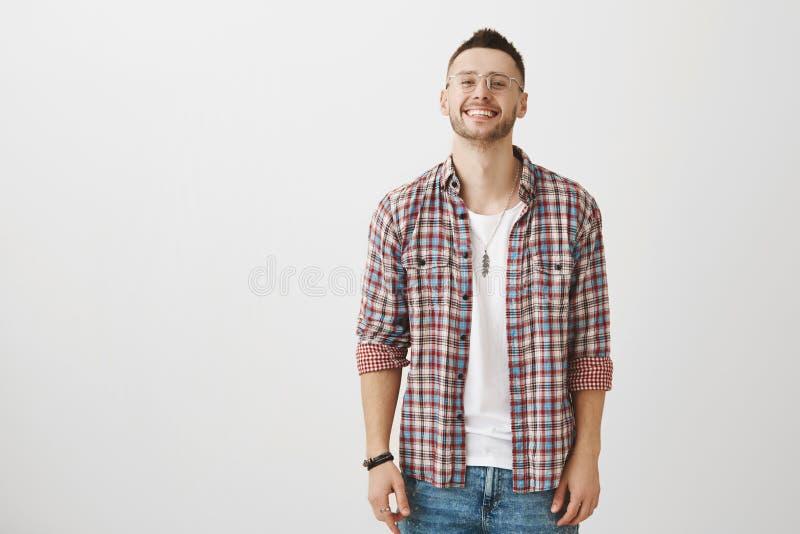 Το χαμόγελο μπορεί να σπάσει τον πάγο Στούντιο που πυροβολείται του όμορφου νεαρού άνδρα με τη σκληρή τρίχα στα διαφανή γυαλιά πο στοκ φωτογραφία με δικαίωμα ελεύθερης χρήσης