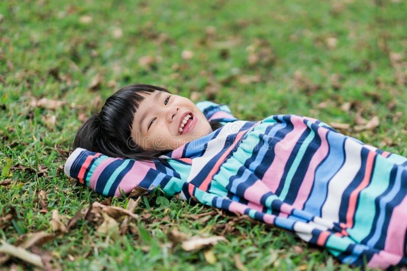 Το χαμόγελο της Νίκαιας του μικρού κοριτσιού όταν χαλαρώστε ξαπλώνει στοκ εικόνα