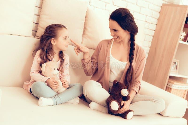 Το χαμόγελο Mom και κόρη κάθεται στον άσπρο καναπέ στο σπίτι στοκ εικόνα με δικαίωμα ελεύθερης χρήσης