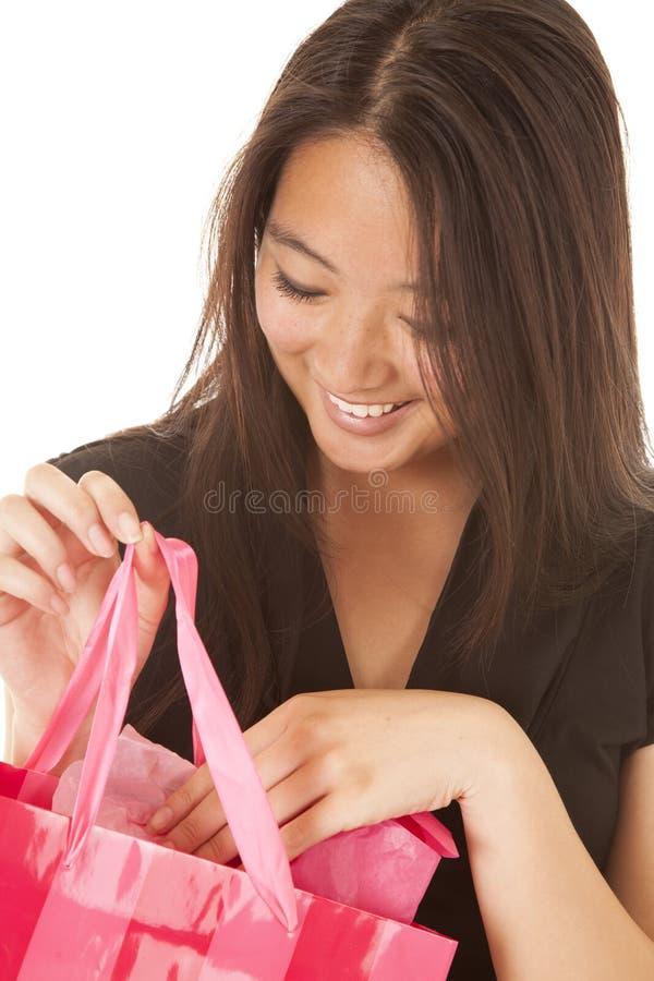 Το χαμόγελο γυναικών κοιτάζει στη ρόδινη τσάντα στοκ φωτογραφία με δικαίωμα ελεύθερης χρήσης
