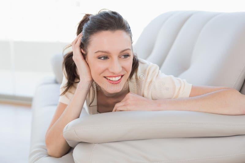Το χαμόγελο χαλάρωσε περιστασιακό να βρεθεί γυναικών στον καναπέ στοκ φωτογραφίες