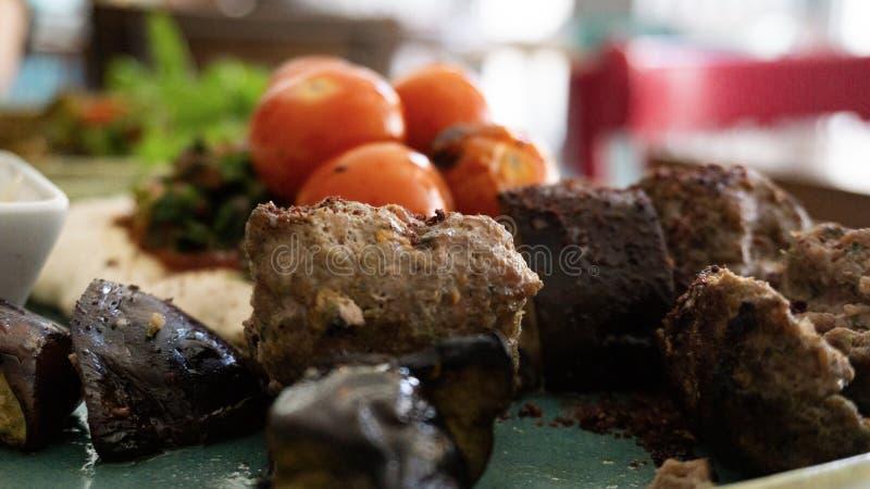 Το χαρακτηριστικό λιβανέζικο πιάτο βασισμένο στα κομμάτια του κρέατος είναι ψημένος κιμάς με μια πλευρά των μαγειρευμένων ντοματώ στοκ φωτογραφία