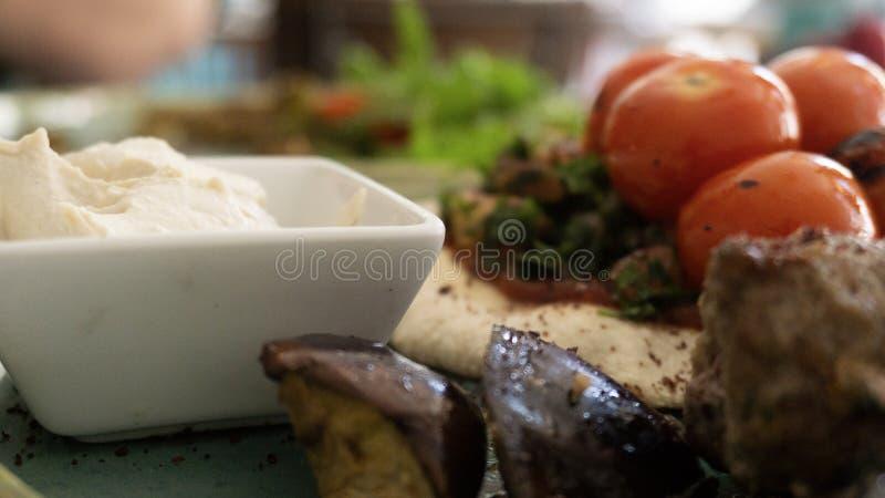 Το χαρακτηριστικό λιβανέζικο πιάτο βασισμένο στα κομμάτια του κρέατος είναι ψημένος κιμάς με μια πλευρά των μαγειρευμένων ντοματώ στοκ εικόνα