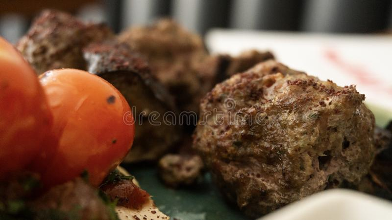 Το χαρακτηριστικό λιβανέζικο πιάτο βασισμένο στα κομμάτια του κρέατος είναι ψημένος κιμάς με μια πλευρά των μαγειρευμένων ντοματώ στοκ φωτογραφία με δικαίωμα ελεύθερης χρήσης