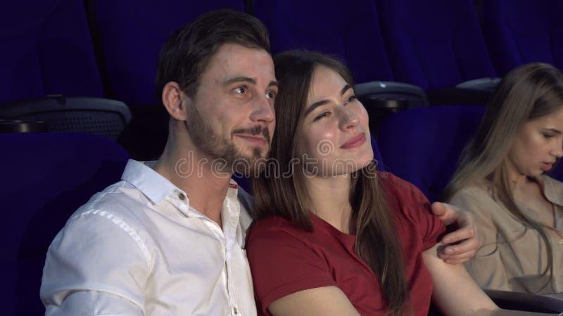 Το χαριτωμένα αγόρι και το κορίτσι κάθονται σε έναν εναγκαλισμό στον κινηματογράφο στοκ εικόνες
