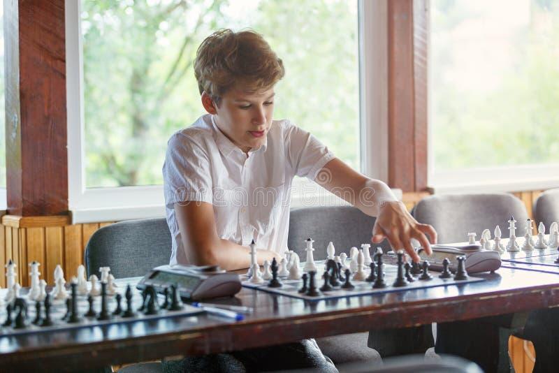 Το χαριτωμένο, έξυπνο, νέο αγόρι στο άσπρο πουκάμισο παίζει το σκάκι στη σκακιέρα στην τάξη Εκπαίδευση, χόμπι, κατάρτιση στοκ φωτογραφία