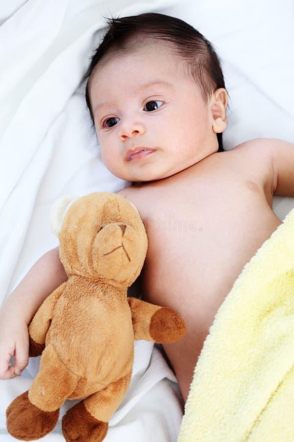 Το χαριτωμένο αγοράκι είναι ευχαριστημένο από το κίτρινο κάλυμμα και η κούκλα αφορά τον καλό φίλο το άσπρο κρεβάτι στοκ εικόνες με δικαίωμα ελεύθερης χρήσης
