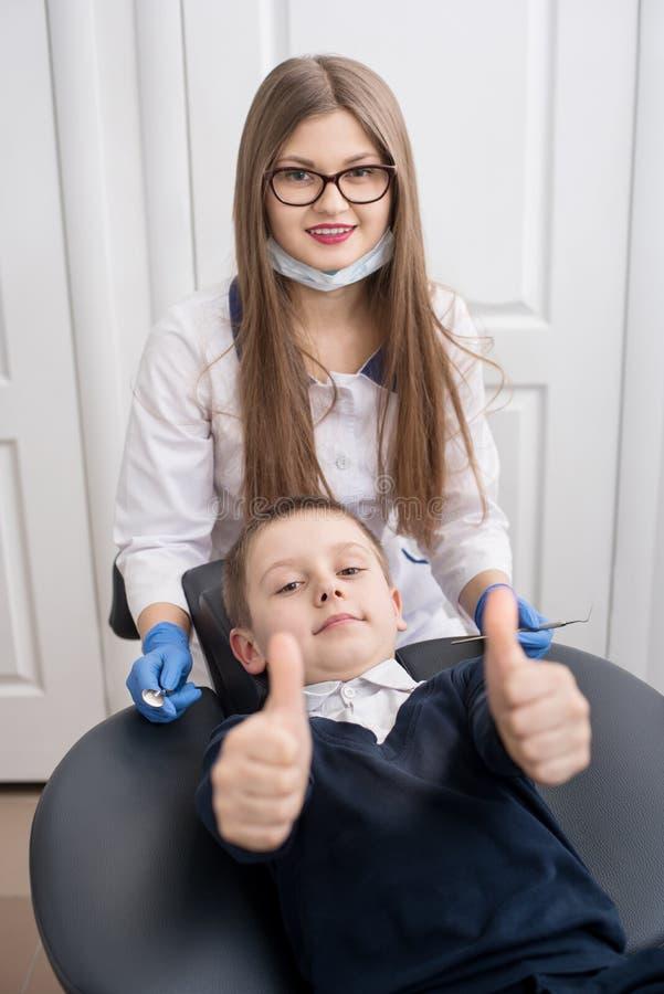 Το χαριτωμένο αγόρι κάθεται σε μια καρέκλα οδοντιάτρων ` s και η παρουσίαση φυλλομετρεί επάνω τις χειρονομίες της καλής κατηγορία στοκ φωτογραφία