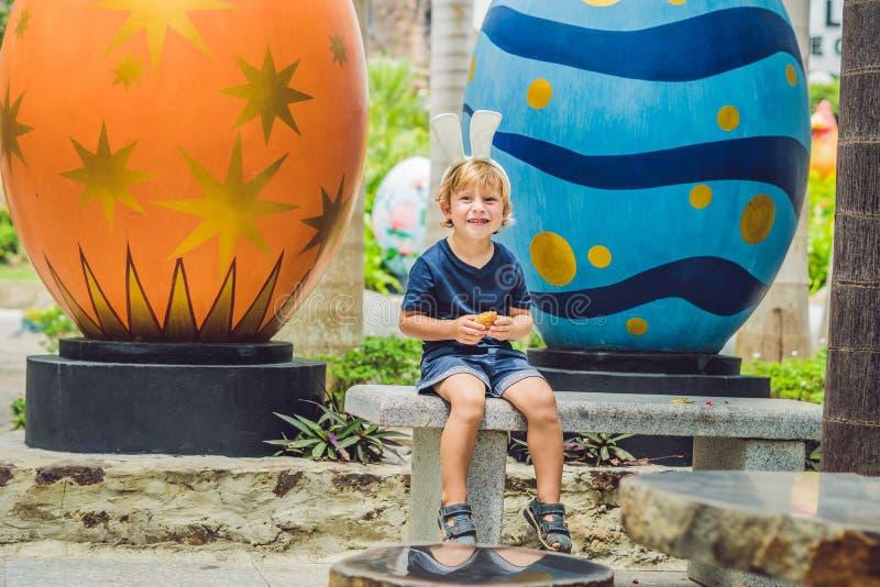 Το χαριτωμένο αγόρι παιδάκι με τα αυτιά λαγουδάκι που έχουν τη διασκέδαση με τα παραδοσιακά αυγά Πάσχας κυνηγά, υπαίθρια Διακοπές στοκ εικόνα με δικαίωμα ελεύθερης χρήσης