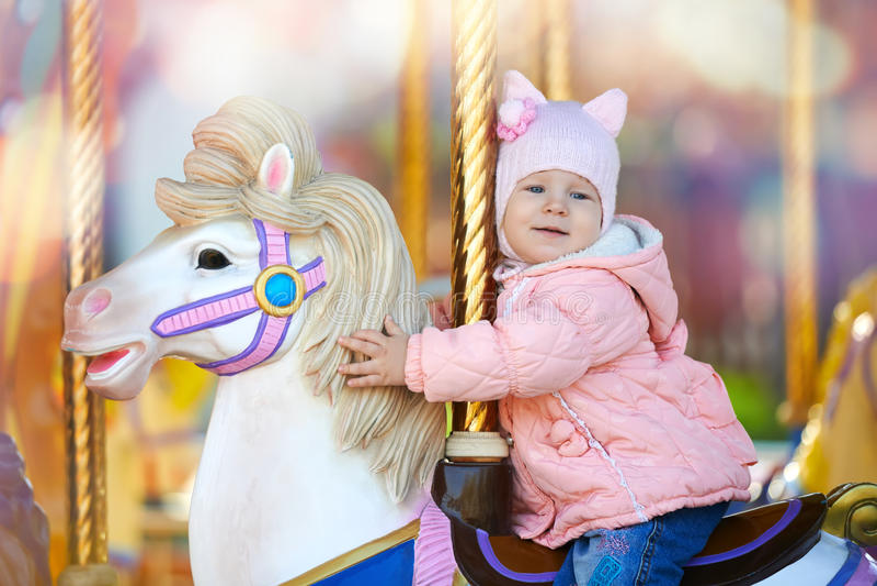Το χαριτωμένο ευτυχές παιδί που οδηγά το άλογο ζωηρόχρωμο στον εύθυμο πηγαίνει γύρω από στοκ φωτογραφία με δικαίωμα ελεύθερης χρήσης