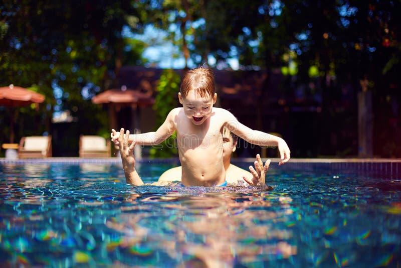 Το χαριτωμένο ευτυχές παιδί πρόκειται να πηδήσει στη λίμνη με τη βοήθεια του μπαμπά του, τροπικές διακοπές στοκ εικόνες