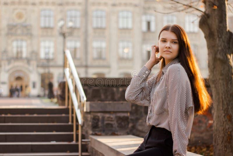 Το χαριτωμένο κορίτσι κάθεται κοντά στα βήματα που οδηγούν στο πανεπιστήμιο στοκ εικόνες με δικαίωμα ελεύθερης χρήσης