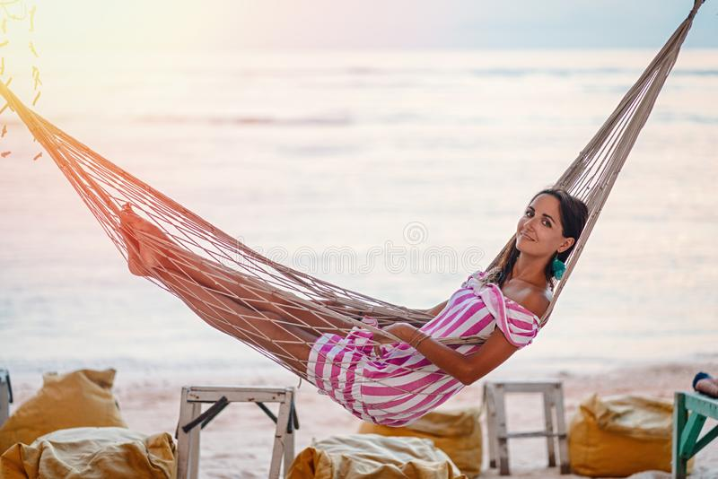 Το χαριτωμένο κορίτσι με ένα χαμόγελο χαλαρώνει να βρεθεί σε μια αιώρα στο υπόβαθρο της θάλασσας στοκ εικόνα