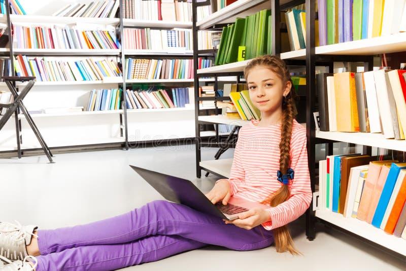 Το χαριτωμένο κορίτσι με την πλεξούδα κρατά το lap-top στη βιβλιοθήκη στοκ εικόνες με δικαίωμα ελεύθερης χρήσης