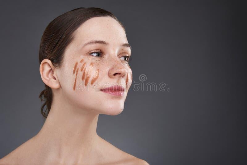 Το χαριτωμένο κορίτσι με το χρυσό χείλι σχολιάζει στο πρόσωπό της που στέκεται στο γκρίζο κλίμα στοκ φωτογραφία