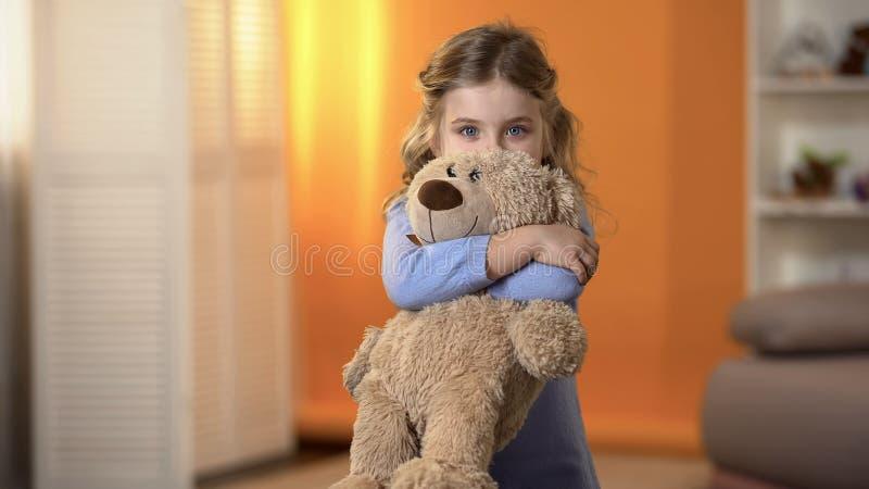 Το χαριτωμένο κορίτσι που αγκαλιάζει αγαπημένο teddy αντέχει και που θέτει για τη κάμερα, ευτυχής παιδική ηλικία στοκ εικόνα με δικαίωμα ελεύθερης χρήσης