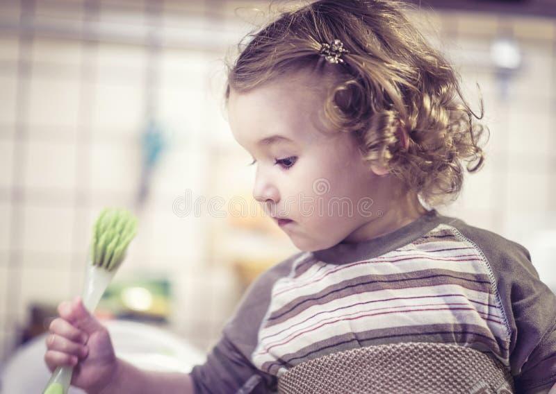 Το χαριτωμένο κοριτσάκι μαθαίνει να πλένει τα πιάτα στην κουζίνα στοκ φωτογραφίες με δικαίωμα ελεύθερης χρήσης