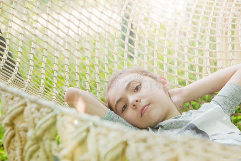Το χαριτωμένο μικρό κορίτσι βρίσκεται στην αιώρα και έχει ένα υπόλοιπο στοκ εικόνες με δικαίωμα ελεύθερης χρήσης