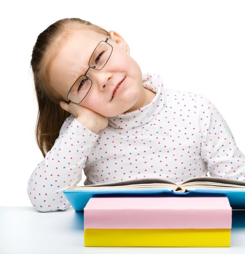 Το χαριτωμένο μικρό κορίτσι είναι κουρασμένο της ανάγνωσης του βιβλίου της στοκ εικόνες με δικαίωμα ελεύθερης χρήσης