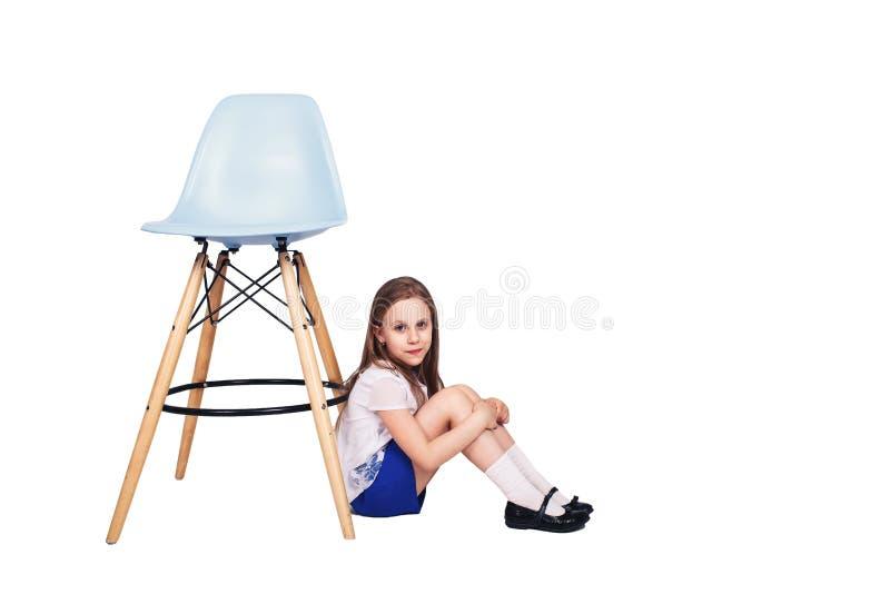 Το χαριτωμένο μικρό κορίτσι κάθεται στο πάτωμα κοντά σε μια κενή καρέκλα κορίτσι λίγη αναμονή Απομονωμένος στο λευκό στοκ εικόνες