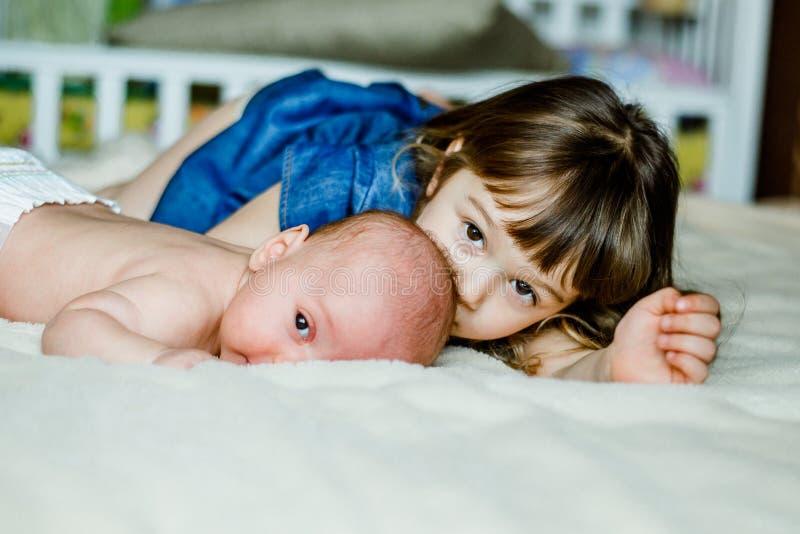 Το χαριτωμένο μικρό κορίτσι παίζει με το μικρότερο αδερφό του στο σπίτι στο κρεβάτι στοκ φωτογραφία με δικαίωμα ελεύθερης χρήσης