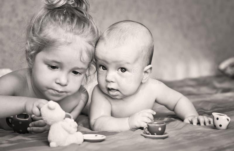 Το χαριτωμένο μικρό κορίτσι παίζει με το μικρότερο αδερφό του στοκ εικόνες