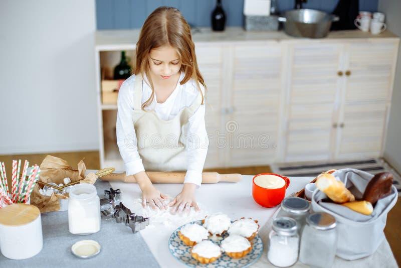 Το χαριτωμένο μικρό κορίτσι στην ποδιά μαγειρεύει τα μπισκότα στην κουζίνα στοκ εικόνα