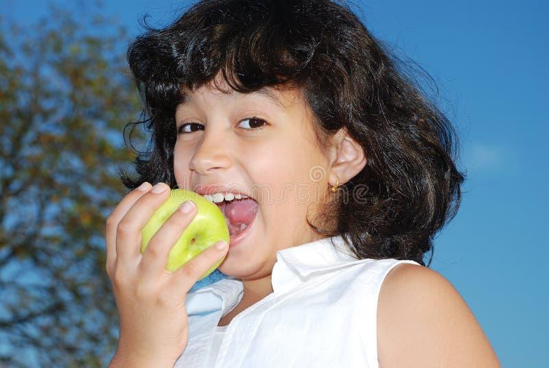 Το χαριτωμένο μικρό κορίτσι τρώει ένα μήλο στοκ εικόνες με δικαίωμα ελεύθερης χρήσης