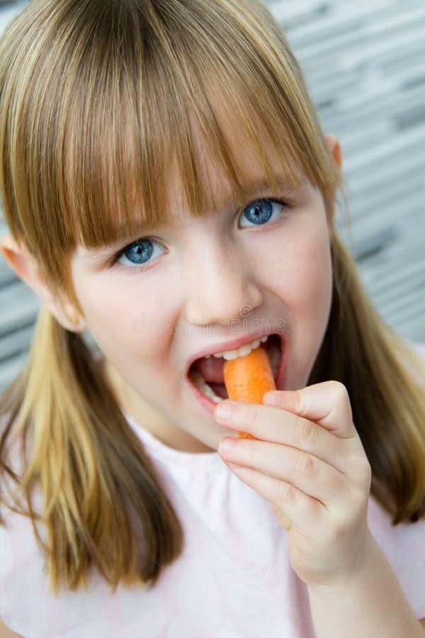 Το χαριτωμένο μικρό κορίτσι τρώει το καρότο και την εξέταση τη κάμερα στοκ εικόνα