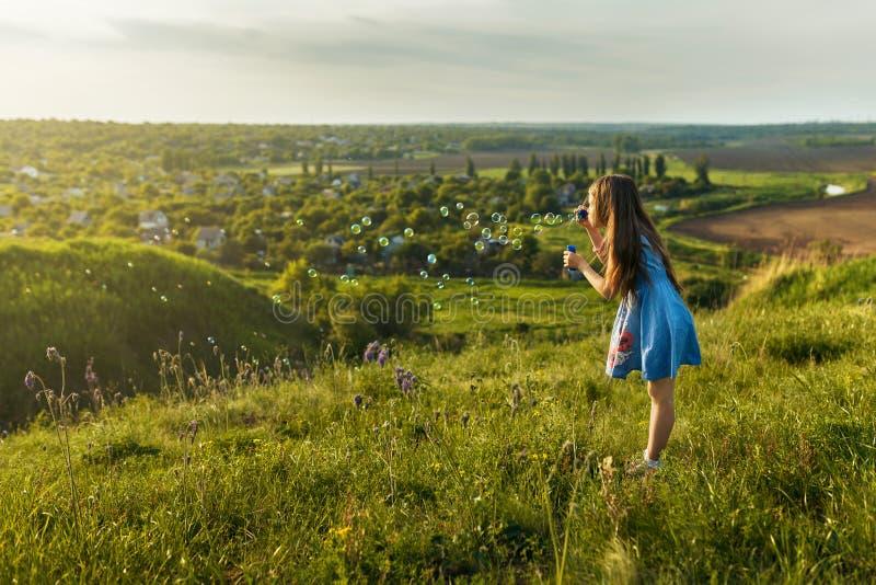 Το χαριτωμένο μικρό κορίτσι φυσά ένα σαπούνι βράζει στοκ φωτογραφίες