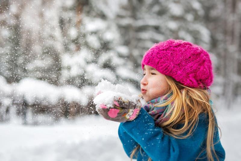 Το χαριτωμένο μικρό κορίτσι φυσά το χιόνι από τα χέρια στοκ φωτογραφία