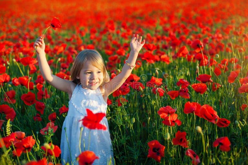 Το χαριτωμένο μικρό κορίτσι χαμογελά και αυξάνει τα όπλα της προς τα πάνω για τη χαρά τομείς παπαρουνών στην Ιταλία στοκ εικόνες