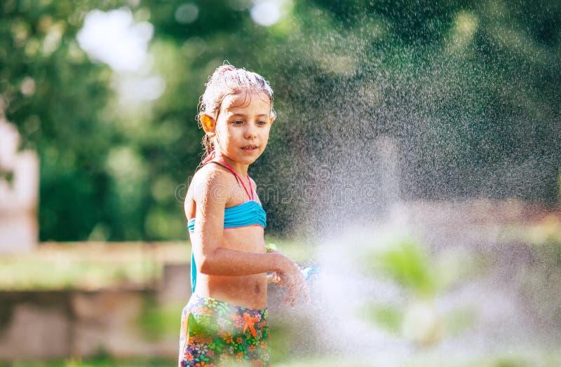 Το χαριτωμένο μικρό κορίτσι sprinkls ένα νερό για την από τη μάνικα, κάνει μια βροχή ευχαρίστηση για τις καυτές θερινές ημέρες Ευ στοκ εικόνα με δικαίωμα ελεύθερης χρήσης