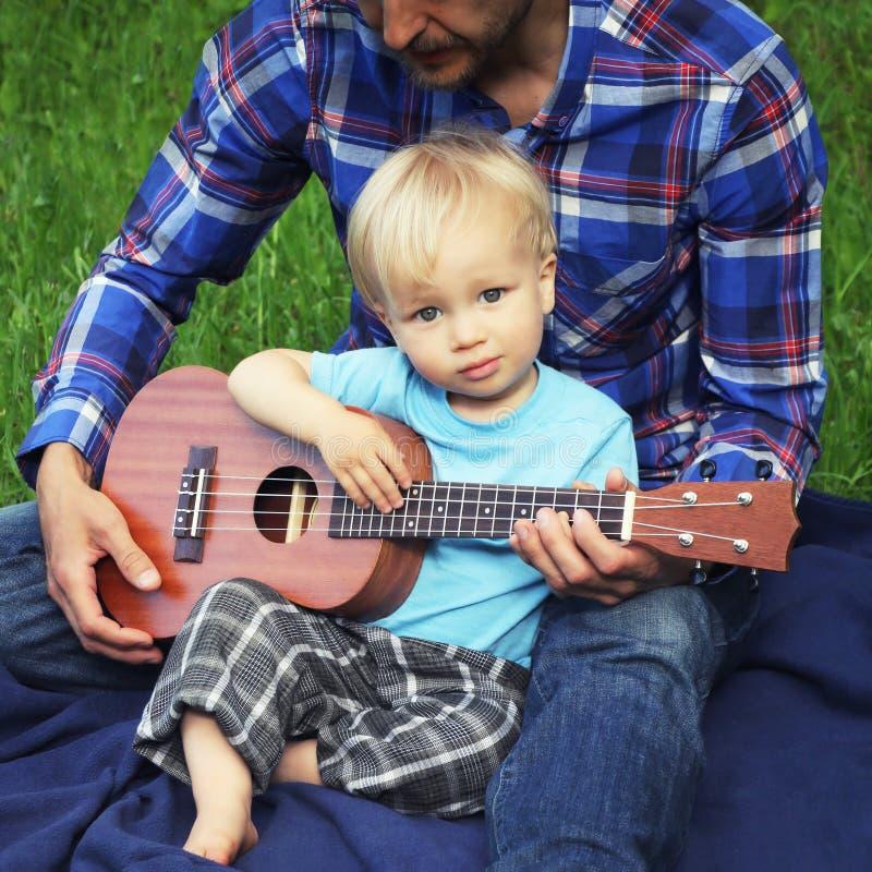 Το χαριτωμένο μικρό παιδί με το ukulele κάθεται στην περιτύλιξη του πατέρα του Ο πατέρας διδάσκει το γιο του για να παίξει στην τ στοκ φωτογραφίες