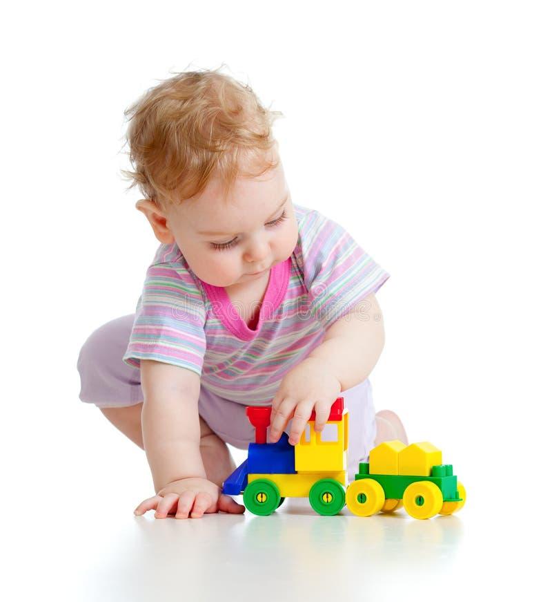 Το χαριτωμένο μικρό παιδί παίζει με το ζωηρόχρωμο τραίνο στοκ εικόνες
