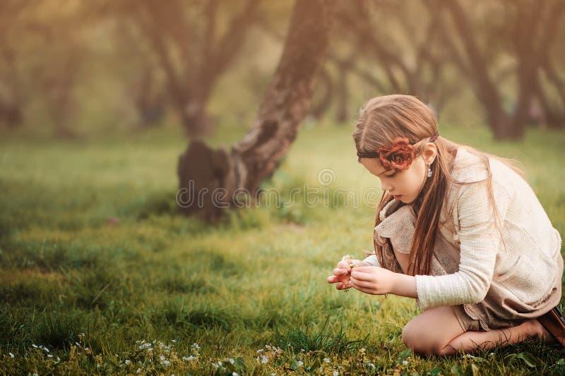 Το χαριτωμένο ονειροπόλο κορίτσι παιδιών στα μπεζ λουλούδια επιλογής εξαρτήσεων καλλιεργεί την άνοιξη στοκ εικόνες